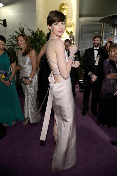 "Actress Anne Hathaway wears a Prada gown as she holds her trophy for Best Supporting Actress for her performance in ""Les Miserables"" after Sunday's Academy Awards."