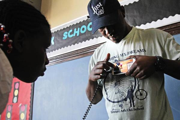 "Seventh grader S'mone Honeycutt, 12, leans in to get a look at the phone of amateur rapper Kris Gordon, aka K-Pilla, who was showing students the trailer of his new anti-violence video called ""Message to My Killer."""