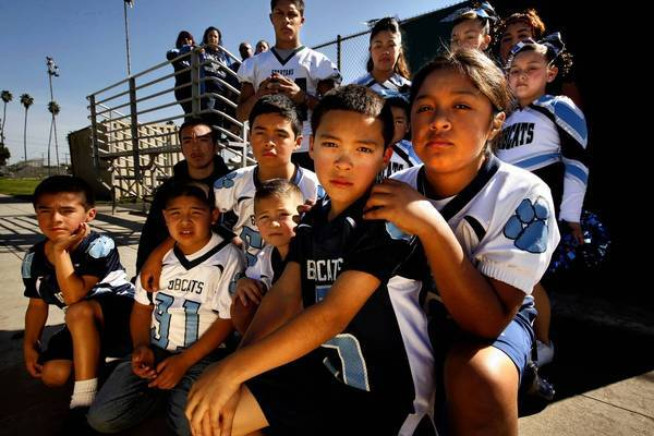 """Bobcat team members past and present, along with Bobcat cheerleaders, parents and supporters, pose for a portrait at Salazar Park in East Los Angeles. """"The whole team, we're like family,"""" said 8-year-old Jacob Ramos, second from right in front."""