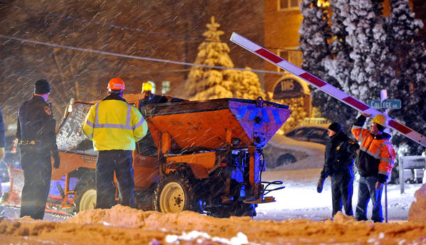 Emergency workers remove a small snowplow from Union Pacific tracks at College Avenue in Wheaton, Ill. The snow plow had overturned, causing delays for commuters.