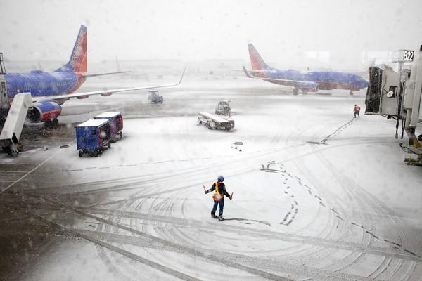 Southwest Airlines employees guide a plane into the gate Tuesday at a snowy Midway International Airport. Many flights were canceled there and at O'Hare.