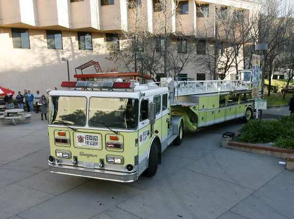 The 1990 Seagrave 100-foot tillered ladder truck makes a tight turn to leave the San Rafael Plaza after a press conference to announce the donation of the truck to Glendale Community College.