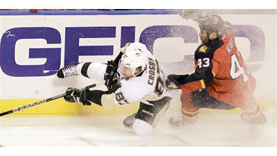 Pittsburgh Penguins' Sidney Crosby (87) falls as Florida Panthers' Mike Weaver (43) defends during the first period of an NHL hockey game Tuesday in Sunrise, Fla.