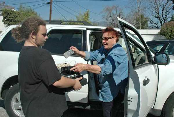 Logan Smith, left, a member of Temple Beth Emet, receives electronics from Burbank resident Ursula Arndt. The temple collected TVs, computers and other electronic waste that was hauled away by All Waste Electronic Recycling in Sun Valley.