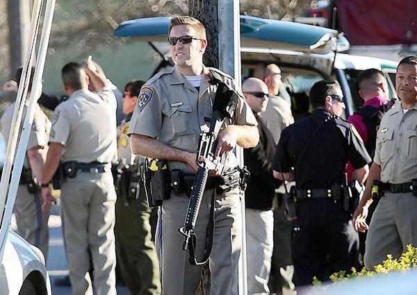 "A California Highway Patrol officer carries a rifle near the shooting scene in Santa Cruz. ""This is a horrific day. We lost two exceptionally fine officers,"" a visibly shaken Chief Kevin Vogel told reporters."