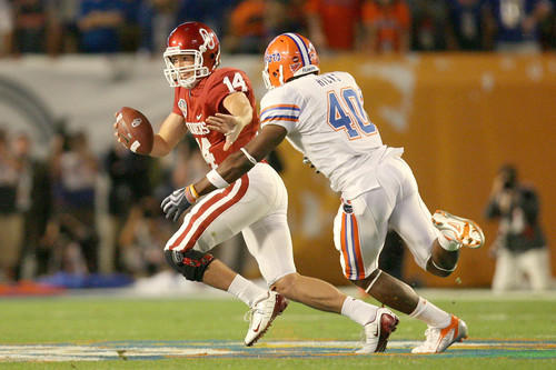 Oklahoma quarterback Sam Bradford (left) attempts to escape the rush from Florida linebacker Brandon Hicks during the BCS national championship game in Miami. The Gators defeated the Sooners, 24-14, to capture their second BCS national title in three years.