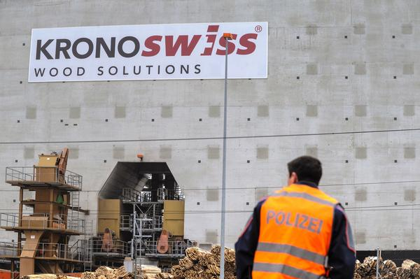A police officer stands on Wednesday outside the Kronoswiss wood panel plant in Menznau, near Lucerne, where three people were killed when a gunman opened fire earlier in the day.