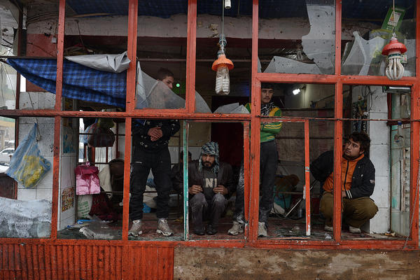 Afghan bystanders look through the blown-out windows of a bakery Wednesday at the scene of a suicide attack against a bus carrying Afghan army personnel in Kabul.