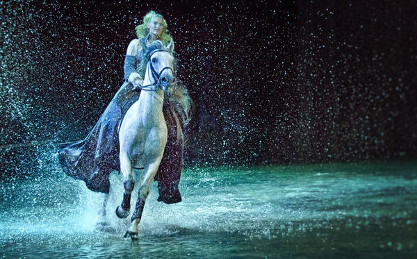 "A Lusitano stallion named Omerio and Elise Verdoncq splash through the 80,000-gallon lake during the finale of ""Cavalia's Odysseo."" No other touring show has attempted to create an onstage lake."