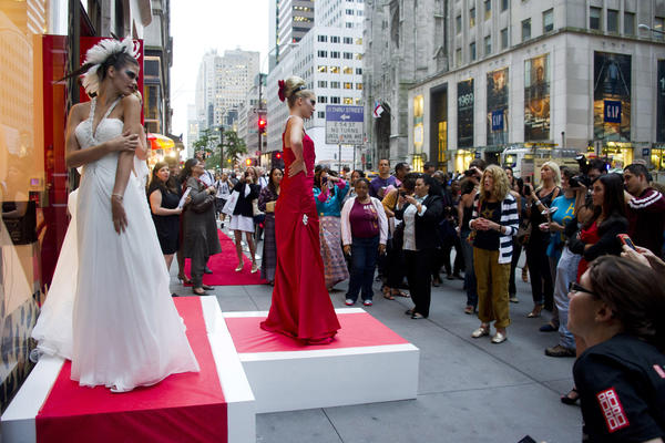 Models pose outside the Elizabeth Arden store on Fifth Avenue during Fashion's Night Out in New York. The annual event has been discontinued for 2013.