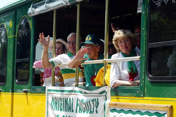 Original faculty members of Glenbrook North, from left, Joyce Hewitt, Cliff Capp, Mickey Johnson and Ellie Dedrick wave from the trolley in which they ride during a Fourth of July parade in Northbrook in 2003.