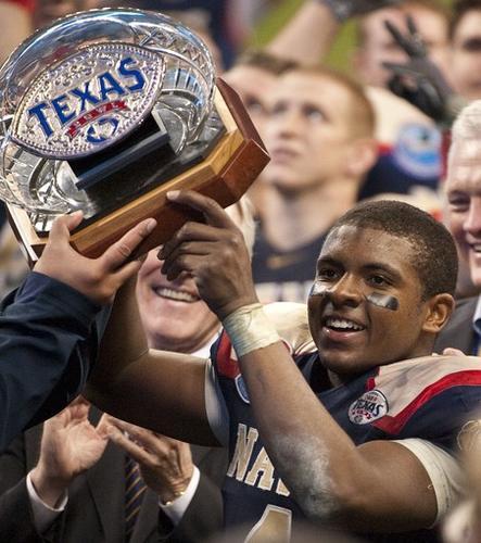 Navy quarterback Ricky Dobbs hoists the Texas Bowl trophy.