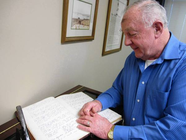 Orland Park Village Clerk David Maher gets out Village Board meeting minutes from 1901 that were preserved during his time in office.