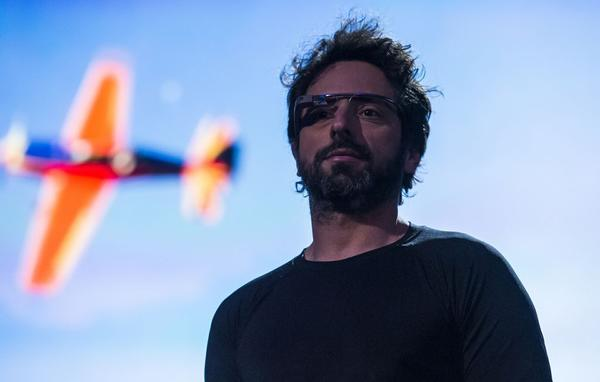 Sergey Brin wearing Google Glass on stage at TED 2013.