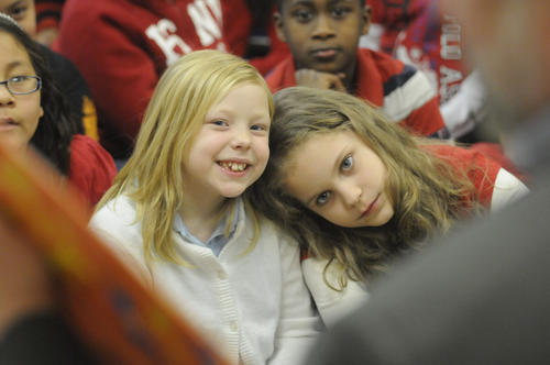 Vance Village School students Mackenzie Robinson, 8, left, and Julie Nalewajek, also 8, look at the pages of a Dr. Seuss book being read by superintendent of schools Kelt Cooper Wednesday afternoon.