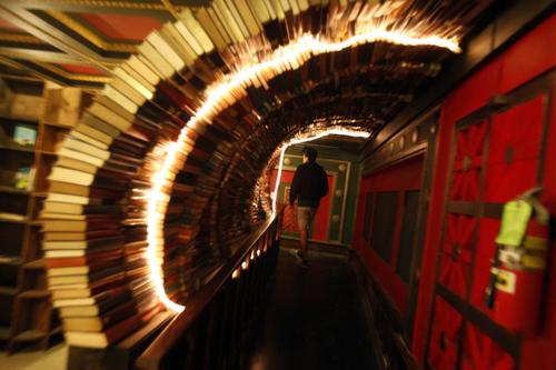 """A visitor walks through a tunnel of books in the Labyrinth on the second floor of the Last Bookstore in downtown Los Angeles. The Labyrinth features a massive, chaotic, maze-like space housing more than 100,000 used books, all at $1 each. It features doors that lead nowhere, time-travel portholes looking into an artist's rendition of outer space, and """"secret passage ways"""" leading into hidden book rooms."""