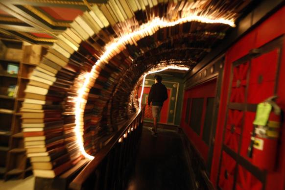 "A visitor walks through a tunnel of books in the Labyrinth on the second floor of the Last Bookstore in downtown Los Angeles. The Labyrinth features a massive, chaotic, maze-like space housing more than 100,000 used books, all at $1 each. It features doors that lead nowhere, time-travel portholes looking into an artist's rendition of outer space, and ""secret passage ways"" leading into hidden book rooms."