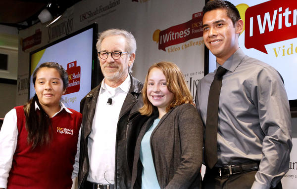 Schindler's List producer Steven Spielberg, center, poses with featured students (l-r: USC Hybrid High School freshman Elizabeth Romero, Director Steven Spielberg, Chandler School 7th grader Corah Forrester and Camino Nuevo High School senior Steven Colin) at Chandler School students after announcement of the IWitness Video Challenge at the Pasadena school on Wednesday, February 27, 2013.  The IWitness Video Challenge is a program for middle and high schools that brings testimonies from holocaust survivors and witnesses into the classroom for guided exploration.