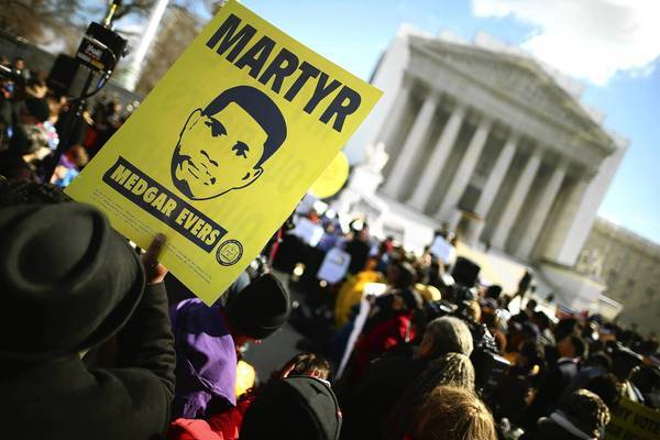 A sign at a rally outside the Supreme Court on Wednesday pictures Medgar Evers, the Mississippi civil rights worker who was slain in a racially charged attack in 1963. The high court is debating a challenge to a section of the 1965 Voting Rights Act.
