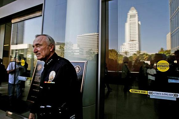 Los Angeles Police Chief William J. Bratton stands in front of the new police headquarters building, with City Hall reflected in the glass behind him.