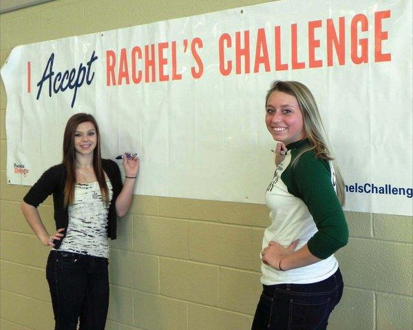 James Buchanan High School students Carley Shaffer and Shaina Haas get ready to sign their names to the Rachel's Challenge pledge board hanging in the high school cafeteria on Wednesday.
