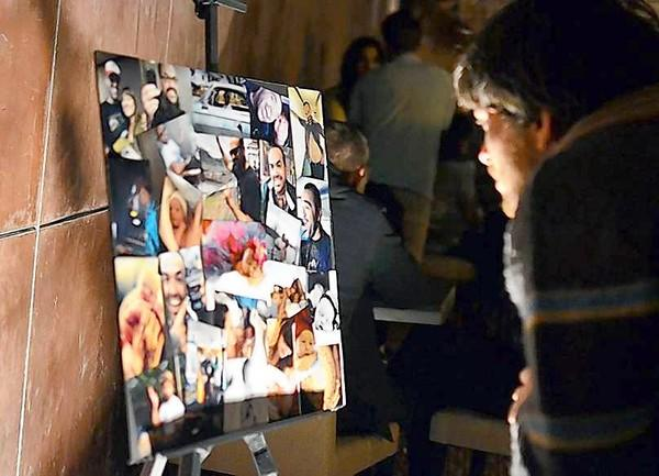 Brennan Roach, an acquaintance of Christian DaSilva, looks at a collage of photos of DaSilva at a benefit concert at the Glass House in Pomona on Saturday night.