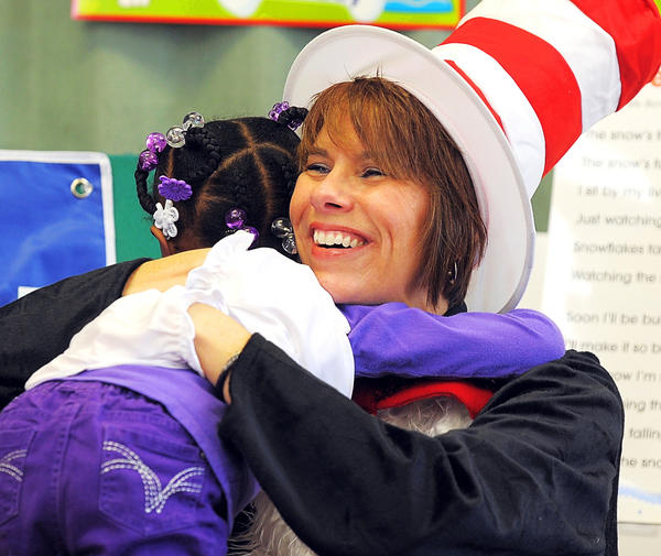 The Dr. Seuss character Cat in the Hat, played by Lisa Conrad, gets a big hug from Spread Your Wings Learning Center Preschool student Aniyah McFarlane Wednesday. The Cat visited classes at the Cleveland Avenue center inside Christ Evangelical Lutheran Church in Hagerstown.