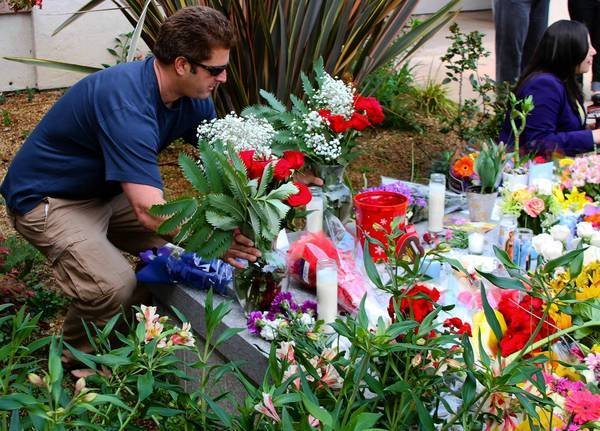 Sky Hall leaves flowers in front of the Santa Cruz Police Department on Wednesday at a memorial for two police detectives who were killed Tuesday. Suspect Jeremy Goulet, 35, was shot and killed by officers.