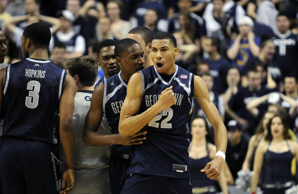 Georgetown Hoyas forward Otto Porter Jr. (22) is mobbed by his teammates after hitting the last shot for the Hoyas giving them a 79-78 victory against the Connecticut Huskies at Gampel Pavilion Wednesday night. Porter scored 22 points in 49 minutes. Ryan Boatright's three-point attempt bounced off the rim at the buzzer.