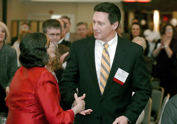 John P. Itell, a partner with Albright, Crumbacker, Moul & Itell CPA, is congratulated by Julianna Albowicz on Wednesday night after he was named Washington County Business Person of the Year at Hager Hall Conference & Event Center in Hagerstown.