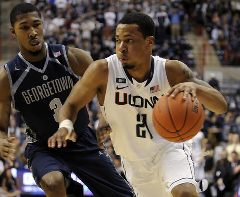 Connecticut Huskies guard Omar Calhoun (21) drives past Georgetown Hoyas forward Mikael Hopkins (3) during the first half at Gampel Pavilion Wednesday night. Calhoun scored 13 points for the Huskies and Hopkins scored 8 for the Hoyas in a 79-78 double-overtime victory for Georgetown.