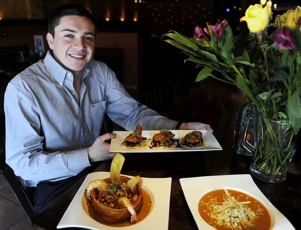 Oscar Longas, manager at Mesa, a modern Mexican restaurant in Easton, holds Crispy Mahi Mahi . Seared Shrimp and Scallops (front left) and Chicken Tortilla Soup