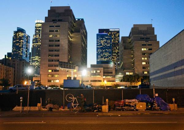 Homeless people gather along Los Angeles Street on skid row. City officials are seeking to overturn a court ruling preventing the removal of homeless people's unattended belongings from sidewalks. The case could have broad implications for other cities.