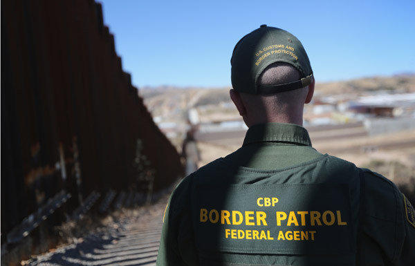 A U.S. Border Patrol agent looks along a section of recently-constructed fence at the U.S.-Mexico border in Nogales, Ariz. The new fencing, which ranges from 18-32 feet high in the Nogales area, allows Border Patrol agents to see through the fence and is harder for immigrants or drug smugglers to scale from the Mexican side.