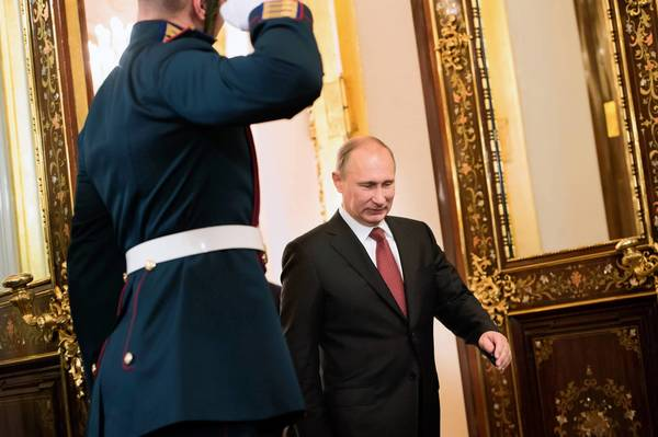 Russian President Vladimir Putin, right, arrives to welcome France's President Francois Hollande prior to their meeting at the Kremlin in Moscow. Hollande is in Moscow to press Putin to engage in efforts to agree a peaceful transition of power in Syria without President Bashar al-Assad.