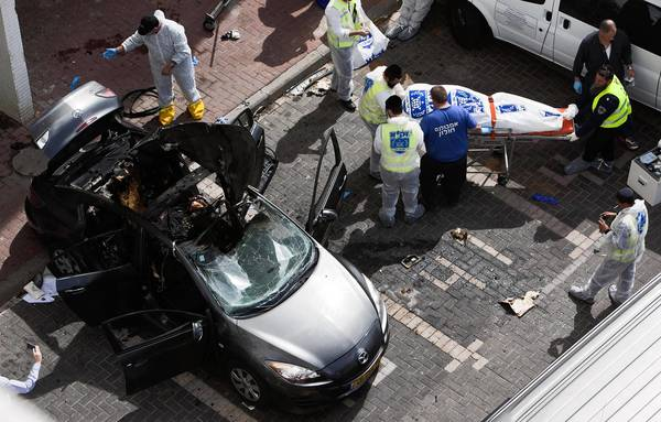 Israeli emergency personnel wheel a body from the scene of an explosion in Rishon Letzion, near Tel Aviv. Israel's Magen David Adom ambulance service said two people died from an explosion in the car.