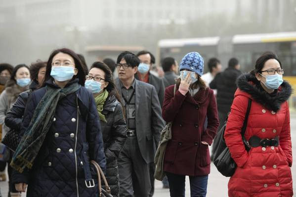 People wearing face masks to protect against heavy pollution walk near the Forbidden City in Beijing. Beijing residents were urged to stay indoors Thursday as pollution levels soared before a sandstorm brought further misery to China's capital.