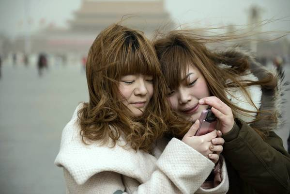 Two women look at a mobile phone as they stand on Tiananmen Square during a sand storm in heavily polluted weather in Beijing. Beijing residents were urged to stay indoors as pollution levels soared before a sandstorm brought further misery to China's capital.