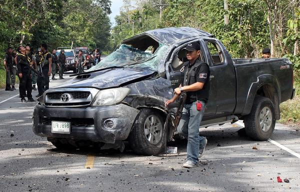 Thai police inspect the site of a bombing by suspected separatist militants in Thailand's southern province of Narathiwat on Feb. 10. The roadside bomb struck a pickup truck carrying army rangers, killing five soldiers, police said.