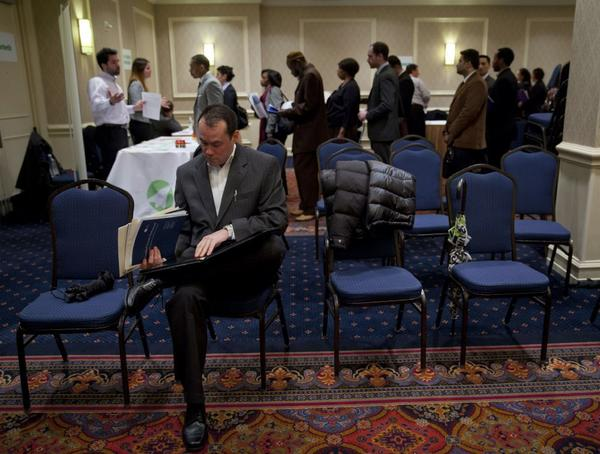 A job seeker looks over paperwork before speaking to recruiters at a job fair organized by United Career Fairs in New York last week.