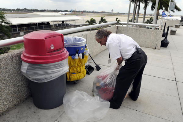 Anthony Bertschi of Sunshine Cleaning removes garbage at the Ft. Lauderdale-Hollywood Airport.