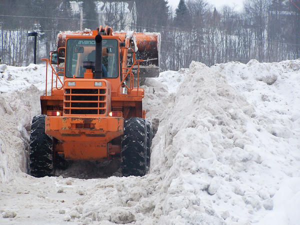 Scooping up the snow at Riverbend Park in Petoskey, this loader is dwarfed by the height of the snow pile.