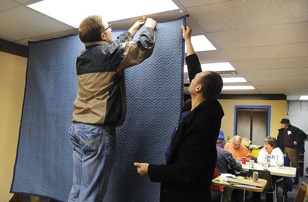 John Paynter, left, and local chiropractor Steven Datson hang a baffle to muffle the sound during the televised Kiwanis auction that begins tonight. The three-day annual auction will be broadcast on Time Warner Cable Channel 5, WKYN 107.7 FM and at winchesterkiwanis.com.