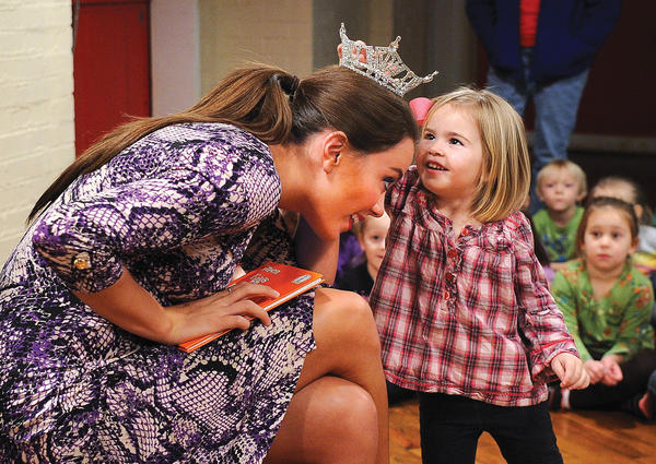 "Miss Kentucky Jessica Casebolt leans over for Brooklyn Arvin to touch her crown during her visit to the Clark County Preschool, top photo. Gabby Yaksich, who wore a ""Cat in the Hat"" hat during the reading, presents Casebolt a gift from the school, middle photo Casebolt was visiting the school to read the Dr. Seuss book ""Green Eggs and Ham"" to the students as part of ""Read Across America Week,"" bottom photo.  Casebolt visited the preschool to thank them for having 100 percent staff participation in the United Way of the Bluegrass campaign."