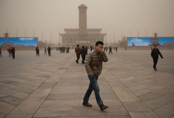 A man covers his face as he walks on Tiananmen Square during a sandstorm in heavily polluted weather in Beijing on February 28, 2013. Beijing residents were urged to stay indoors as pollution levels soared before a sandstorm brought further misery to China's capital.
