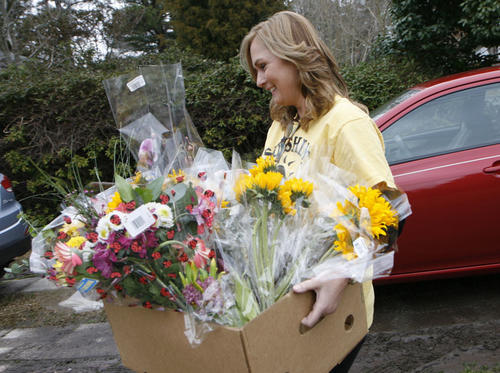 Nicola Fuller carries in a box of donated flowers, which will be arranged in vases and delivered to nursing homes.