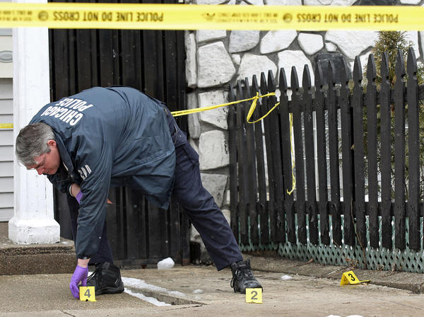 A police officer places evidence markers at the scene the 4800 block of South Paulina Street where a youth was wounded in a shooting.