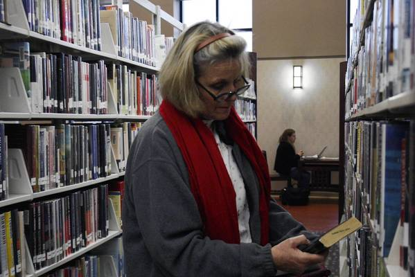 Glenview resident Barbara Carolan browses the shelves at the Glenview Public Library for the next book she would want to read on Friday, Feb. 22. The Village of Glenview recently decided to not pursue the creation of a separate library district at its meeting.