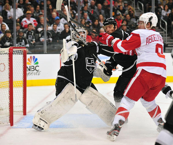 Los Angeles Kings defenseman Rob Scuderi (7) helps defend as goalie Jonathan Bernier (45) hits the puck away against Detroit Red Wings left wing Justin Abdelkader (8) during the second period at Staples Center.