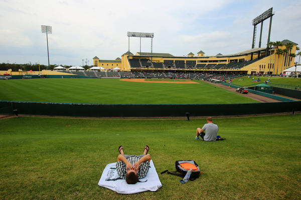 Baseball fans lie in the grass behind the left field wall during the Miami Marlins and Atlanta Braves Grapefruit League Spring Training game at Walt Disney World's Champion Stadium in Lake Buena Vista, Fla.